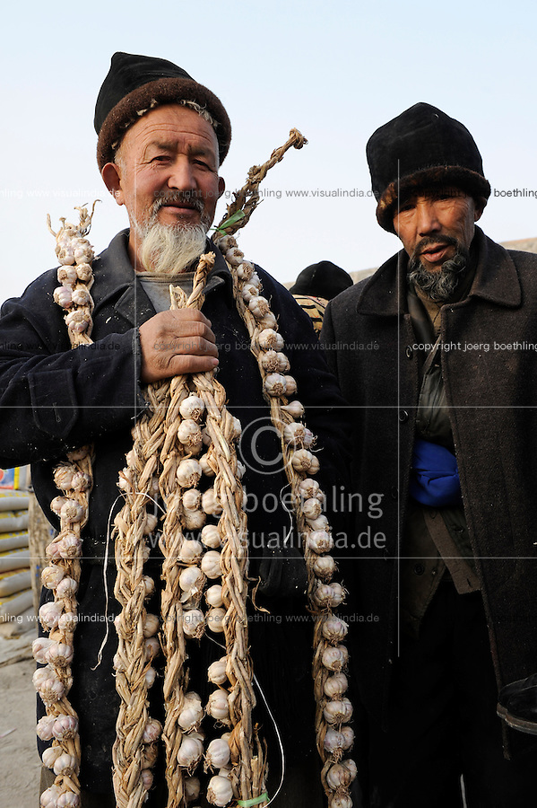 CHINA, province Xinjiang, market day in uighur village Jin Erek near city Kashgar where uyghur people are living, farmer with garlic / CHINA Provinz Xinjiang , Markttag in Jin Erek einem uigurischen Dorf bei Stadt Kashgar, hier lebt das Turkvolk der Uiguren , die sich zum Islam bekennen