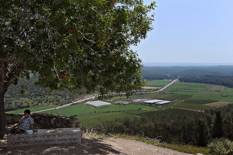 An Ultra-Orthodox Jewish kid sits on a monument, on which a Biblical verse is carved, describing the story of David and Goliath, in a site overlooking Elah Valley.