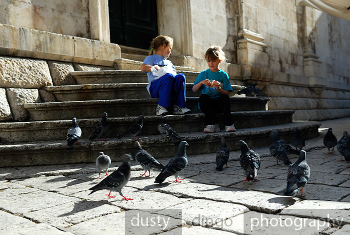 Ground-level view of two children (9 years old, 5 years old) feeding pigeons on Gunduliceva Poljana (Square), Dubrovnik old town, Croatia