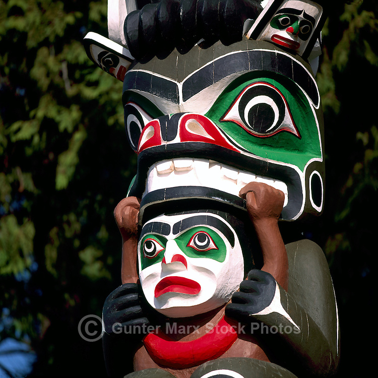Kwakwaka'wakw (Kwakiutl) Totem Pole, called Ga'akstalas, at Brockton Point, Stanley Park, Vancouver, BC, British Columbia, Canada - Close Up Detail.  Grizzly Bear is holding Man's Head.