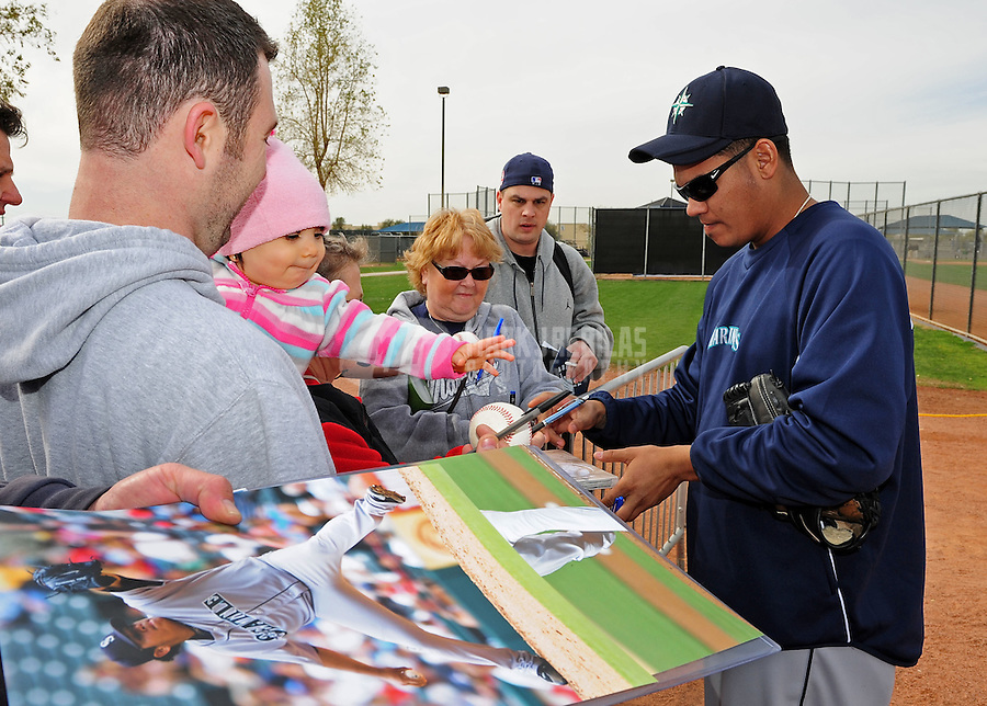 Feb. 15, 2012; Peoria, AZ, USA; Seattle Mariners pitcher Felix Hernandez (right) signs autographs for fans during a pitchers and catchers workout at the Peoria Sports Complex.  Mandatory Credit: Mark J. Rebilas-.