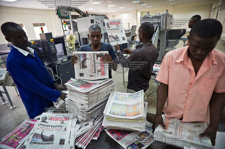 Charles Kabonero (centre right), managing director of Newsline, reading a copy as it comes off the printing press. Charles and his colleagues had to flee to Uganda after their independent weekly Umuseso newspaper was banned in their native country. Now working in exile in Kampala, Charles and his colleagues started a new newspaper Newsline.