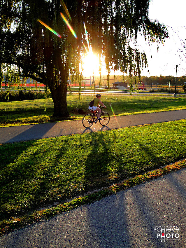 A bicyclist rides in the late afternoon sun on the University of Wisconsin-Madison campus.
