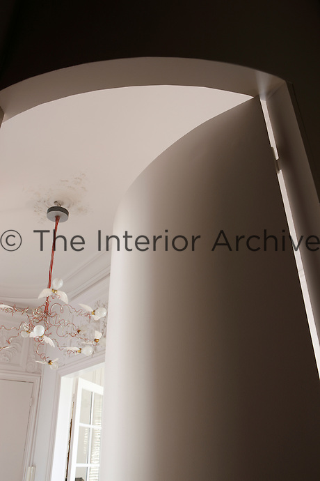 The chandelier in the entrance hall is glimpsed through the curved open door of the kitchen