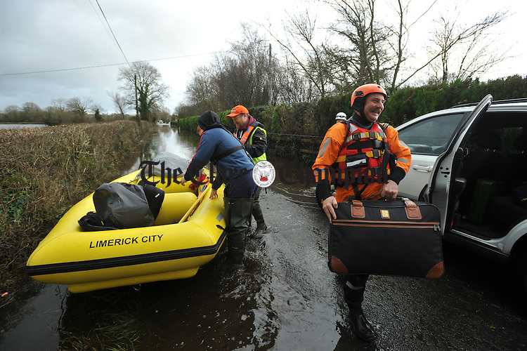 Emergency service personell help with belongings  after they evacuated Mike Hogan and his sons Mark and Sean Hogan by boat from their home at Springfield Clonlara where they were cut of by the flood waters. Photograph by John Kelly.
