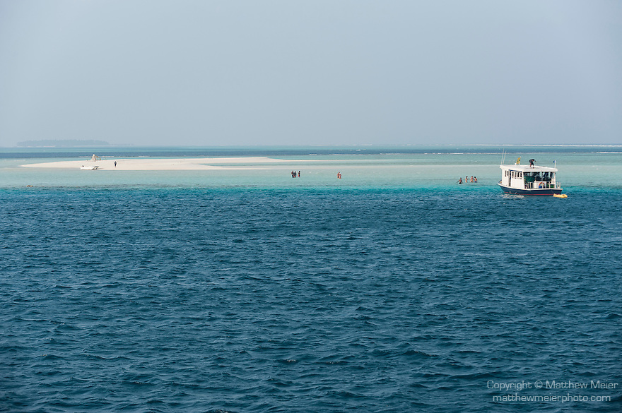 Devana Kandu, Finolu Island, Felidhoo Atoll, Maldives; a view of the small sandbar island of Finolu with people walking through the shallow water to get back to the boat