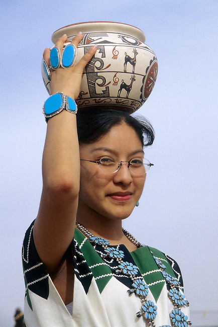 Teenage Zuni girl holds a clay pottery jar on top of head and wears the traditional dress and turquoise squashblossom, rings and bracelet.