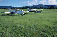 Two planes sitting side by side in the field of the Port Vila Airport, Efate Island, Vanuatu.
