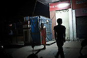 A young man walks up to a sex worker wait for customers outside a night club in Thamel in capital Kathmandu, Nepal