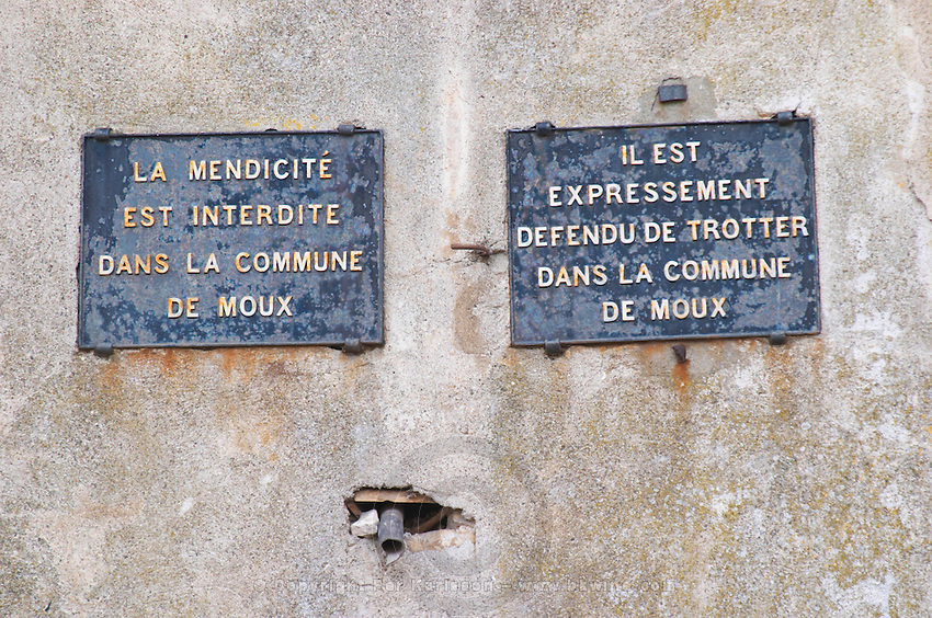 Signs saying: It is forbidden to beg in the commune of Moux. It is explicitly forbidden to loiter (trotter) in the commune of Moux... Les Corbieres. Languedoc. France. Europe.