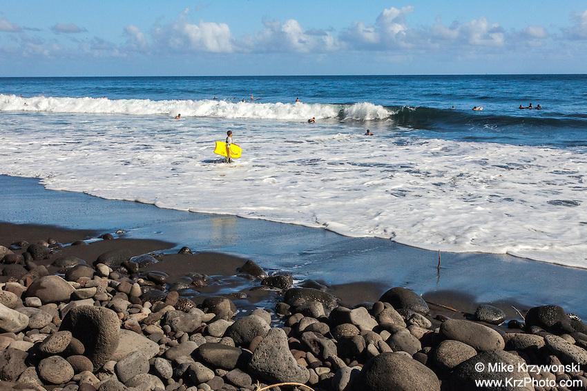 Surfers in the water in Waipio Valley, Big Island, Hawaii