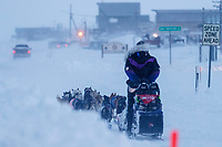 Jessie Royer runs down Front Street with a police escort in a wind-storm as she makes her way toward the Nome finish line to place 3rd in the 2019 Iditarod sled dog race.<br /> <br /> Photo by Jeff Schultz/  (C) 2019  ALL RIGHTS RESERVED