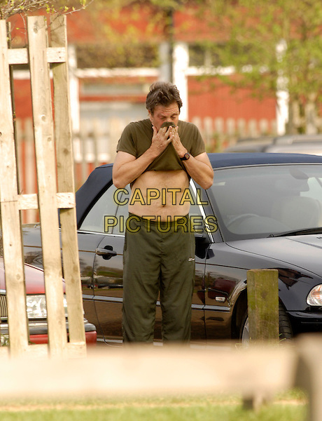MICHAEL BRANDON.Limbering up in Richmond Park, London, .17th April 2007..half length 3/4 wiping face with green khaki t-shirt t shirt funny tummy stomach exercising working out tracksuit bottoms.CAP/P8.©Capital Pictures.