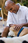 Man petting his dog and smiling