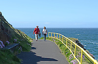 Couple walk around Ramore Head, Portrush, Co Antrim, N Ireland, UK, 201306012512<br />