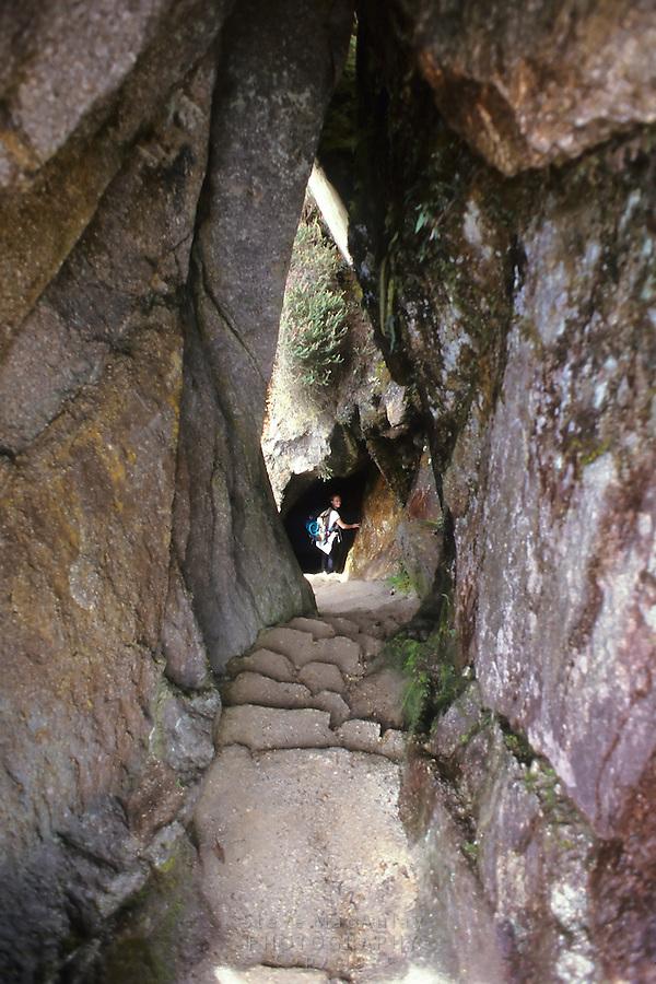 Female hiker descending through a gap in the rock face on the Inca Trail, Peru