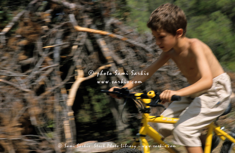 Boy having fun speeding on his mountain bike on a summery day.