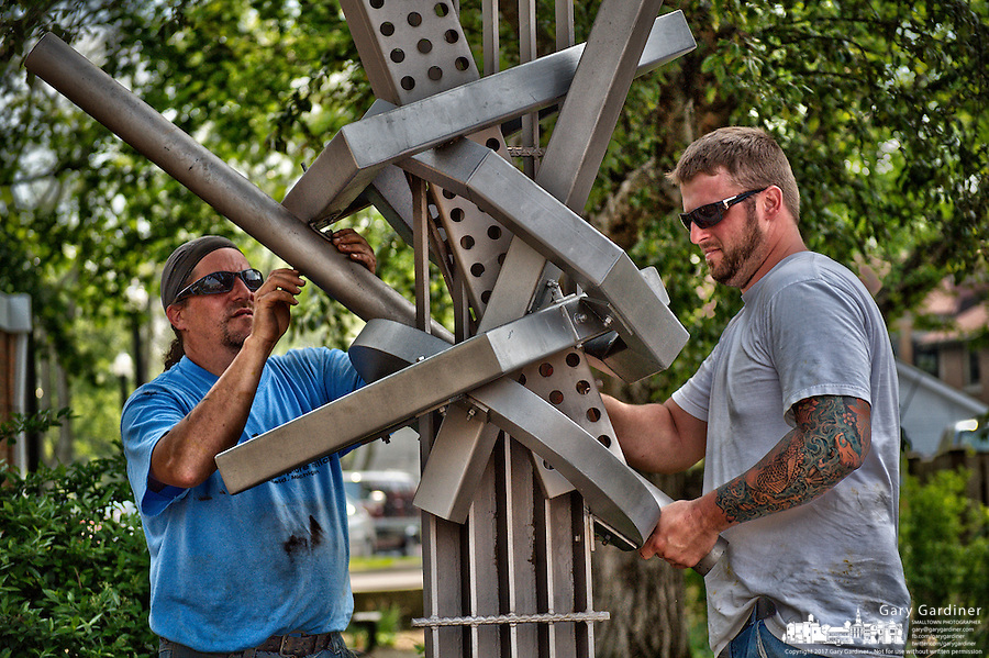 Workers install one of a series of art pieces installed in Westerville, Ohio as part of a year long public display of art.