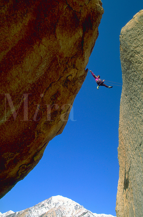 A climber suspended by ropes between two rock faces during a tyrolean traverse, Basin Mountain, Eastern Sierra, California.