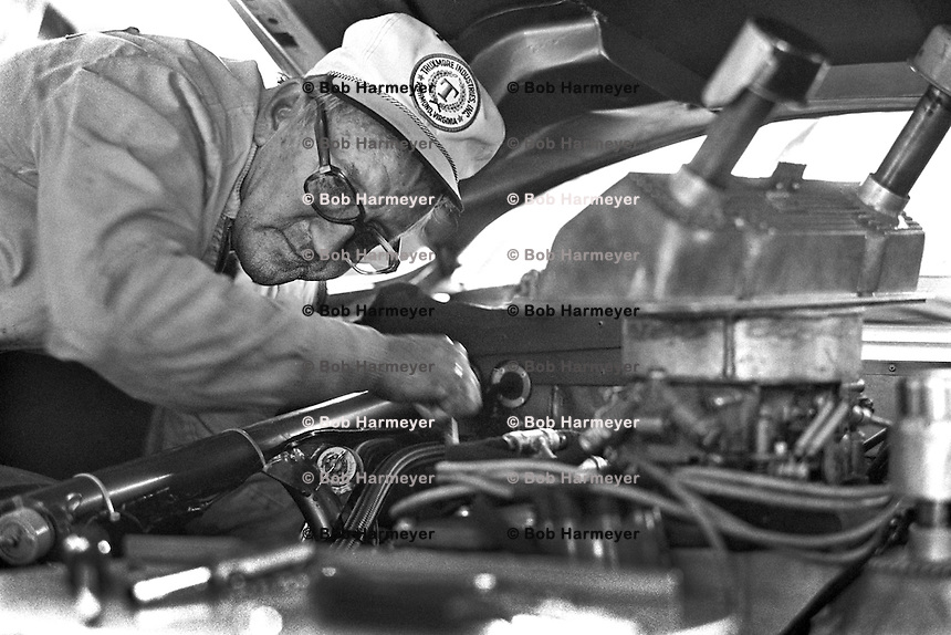 DARLINGTON, SC - APRIL 11: Owner Junie Donlavey works on the engine of his Truxmore Industries Ford driven by Dick Brooks in the Rebel 500 NASCAR Winston Cup Race at the Darlington Raceway near Darlington, South Carolina, on April 11, 1976.