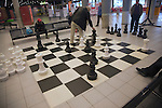 Men playing chess on a giant set in the public library, Rotterdam, South Holland, Netherlands