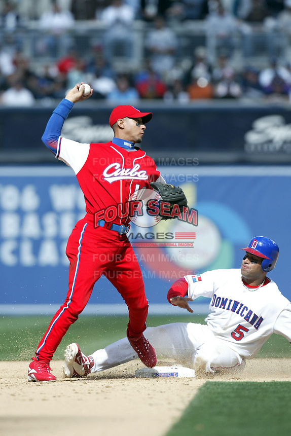 Yulieski Gourriel of the Cuban national team throws to first base after forcing out Albert Pujols of the Dominican Republic team at second base during the World Baseball Championships at Petco Park in San Diego,California on March 18, 2006. Photo by Larry Goren/Four Seam Images