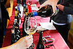 White wine is being poured into a wine glass with two hands showing during a wine tasting event.  Wine bottles are seen lined up on the red clothed tables.