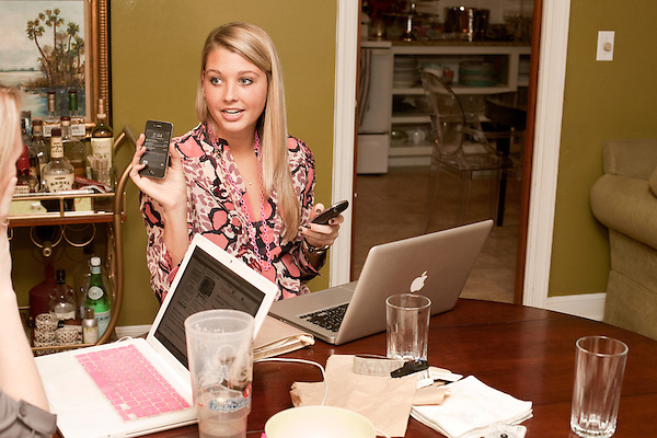 November 27, 2012. Charleston, South Carolina.. In the dining room of her boss Lizz Akerman, Alexa Wyatt looks over voicemails and emails with coworker Sara Hosch.. Alexa Wyatt, 23, is an Event Coordinator with Southern Protocol, a boutique wedding and event planning company in Charleston, SC..