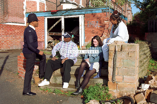 Teenagers sitting on steps on street corner talking with community policeman,
