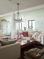 In the living room two white sofas from Ilva are dressed in patterned cushions and quilts, while a Gustavian crystal chandelier hangs above a coffee table imported from Thailand