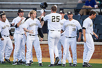 Matt Conway (25) of the Wake Forest Demon Deacons is greeted by his teammates following his second home run on the night against the Maryland Terrapins at Wake Forest Baseball Park on April 4, 2014 in Winston-Salem, North Carolina.  The Demon Deacons defeated the Terrapins 6-4.  (Brian Westerholt/Four Seam Images)