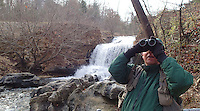NWA Democrat-Gazette/FLIP PUTTHOFF<br /> Joe Neal looks for birds Dec. 1, 2015 along the Tanyard Creek Nature Trail in Bella Vista. Neal scans the forest at a waterfall formed by the spillway at Lake Windsor. Several species of large and small birds were seen on the two-mile hike.