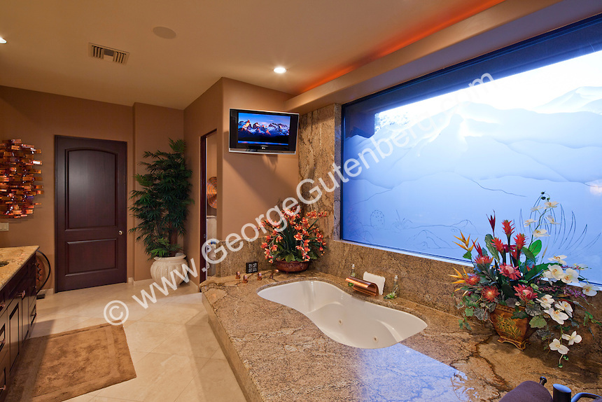 Jacuzzi Style Tub Is Shown In Luxury Bathroom With Large Etched Window And TV Stock Photo