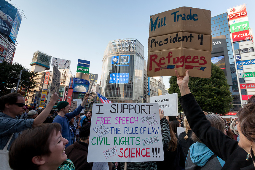 "President Donald Trump appears as a news item on big screens as a woman holds a  sign reading ""will trade President for Refugees"" at the Vote Out the Scandal rally at Hachiko Square, Shibuya, Tokyo, Japan. Sunday November 5th 2017. Timed to coincide with President Trumps visit to Japan, About 120 Americans living in Japan and some local Japanese  protested together from 2pm to 4pm to encourage US citizens to register to vote in future elections and call on the US government to honour it responsibilities to the American people,."