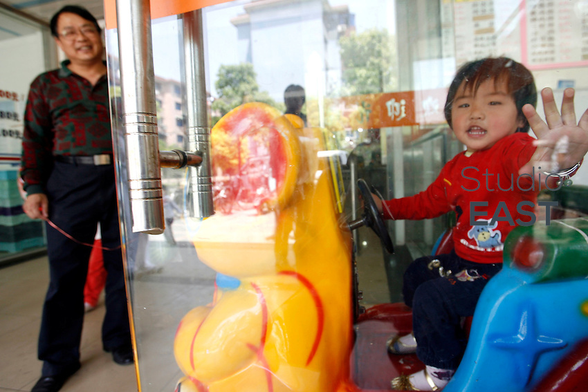 Li Fang (gauche) paie un tour de manège à sa petite-fille Li Siqi (droite) qui est derrière une porte en verre, lors d'une promenade à Baoshan, près de Shanghai, le 7 mai 2008. L'enfant sait parfaitement comment fonctionnent les manèges et où mettre la pièce pour les faire fonctioner. Comme la plupart des enfants du quartier font avec leurs grands-parents, elle réclame un tour dès qu'elle voit un manège au loin. Li Fang refuse rarement. Photo par Lucas Schifres/Pictobank