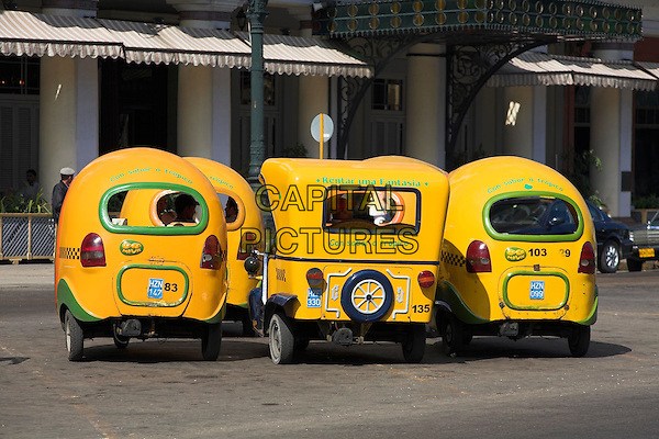 Several yellow three wheeled taxis parked at a taxi rank, Havana, Cuba