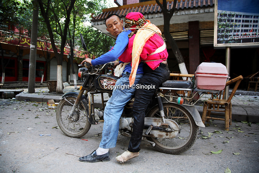 A man looks back at his dead wife, strapped to himself on a motorcycle, in Hanwang, Sichuan, China. Rescue workers have given up on finding people still alive and began to use heavy machinery..14 May 2008