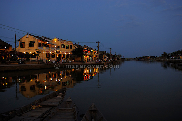 Asia, Vietnam, Hoi An. Hoi An old quarter. View across Thu Bon river onto the beautiful Bach Dang river promenade with it's romantic restaurants. The historic buildings, attractive tube houses, and decorated community halls have 1999 earned Hoi An's old quarter the status of a UNESCO World Heritage Site. To protect the old quarter's character stringent conversation laws prohibit alterations to buildings, as well as the presence of cars on the roads.