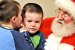 Santa, played by Bob White of Suffield, is taken by surprise while taking the wish list of Daniel Jamrog, 3, of Suffield, his older brother Jack, 4 1/2,  who had already seen Santa, whispers in his younger brothers ear to remind Santa about the trucks that both boys wanted, Tuesday evening, December 9, 2008, at the Suffield Library. (Jim Michaud/Journal Inquirer)