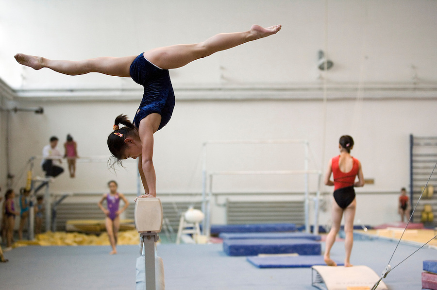 A girls works on a balance beam.