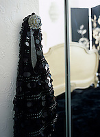A black sequined handbag hangs on the crystal knob of the open bedroom door