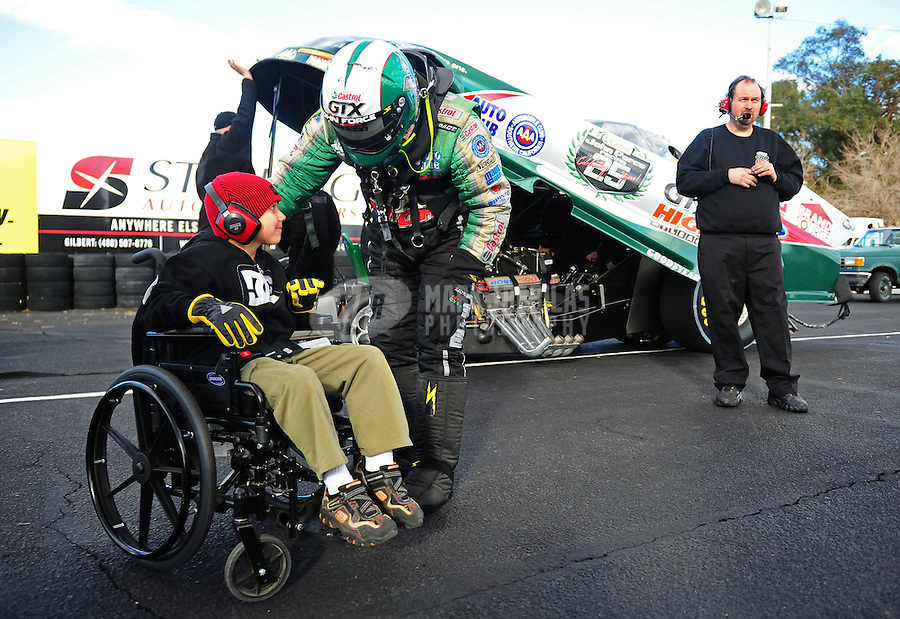 Jan 23, 2010; Chandler, AZ, USA; NHRA funny car driver John Force talks to a young boy prior to climbing into his car during testing at the National Time Trials at Firebird International Raceway. Mandatory Credit: Mark J. Rebilas-