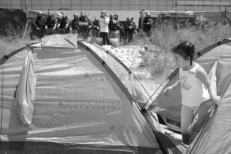 Roma, 29 Maggio 2015<br /> La polizia sgombera le famiglie che avevano occupato ieri il palazzo di vetro in  via Cristoforo Colombo dove ha sede il centro direzionale di confcommercio.<br /> Una bambina gioca davanti lo schieramento della polizia.<br /> Tendopoli nello spazio antistante il palazzo occupato presidiato dalla polizia