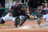 Northwest Arkansas Naturals catcher Meibrys Viloria (22) tries to apply a tag on Midland RockHounds infielder Mikey White (5) on May 4, 2019, at Arvest Ballpark in Springdale, Arkansas. (Jason Ivester/Four Seam Images)