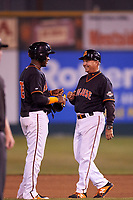 San Jose Giants shortstop Manuel Gerardo (26) hands his protective gear to first base coach Gary Davenport (12) during a California League game against the Visalia Rawhide on April 12, 2019 at San Jose Municipal Stadium in San Jose, California. Visalia defeated San Jose 6-2. (Zachary Lucy/Four Seam Images)