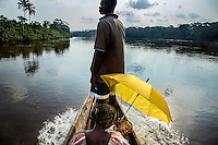 Ophthalmologist Dr Richard Hardi and his team, including a mother and child sheltering beneath an umbrella, travelling in a canoe on the Sankuru River during a medical expedition to the remote village of Pania. <br /> <br /> From his base in Mbuji Mayi Hungarian ophthalmologist Friar Richard Hardi and his team travelled deep into the Congolese rainforest, by 4x4 and canoe, to treat people in isolated communities most of whom have never seen an ophthalmologist. At a small village called Pania they established a temporary field hospital and over the next three days made hundreds of consultations. Although both conditions are preventable, many of the patients they saw had Glaucoma or River Blindness (onchocerciasis) that had permanently damaged their eyesight. However, patients with cataracts, a clouding of the eye's lens, who were suitable for treatment were booked for an operation. For two days the team carried out the ten minute procedure on one patient after another. The surgery involves making a 2.2mm incision into the remove the damaged lens that is then replaced by an artificial one. Doctor Hardi is one of the few people willing to make such a journey but is inspired to do so by his faith and, as he says: 'Here I feel that I can really make a difference in people's lives'. /Felix Features