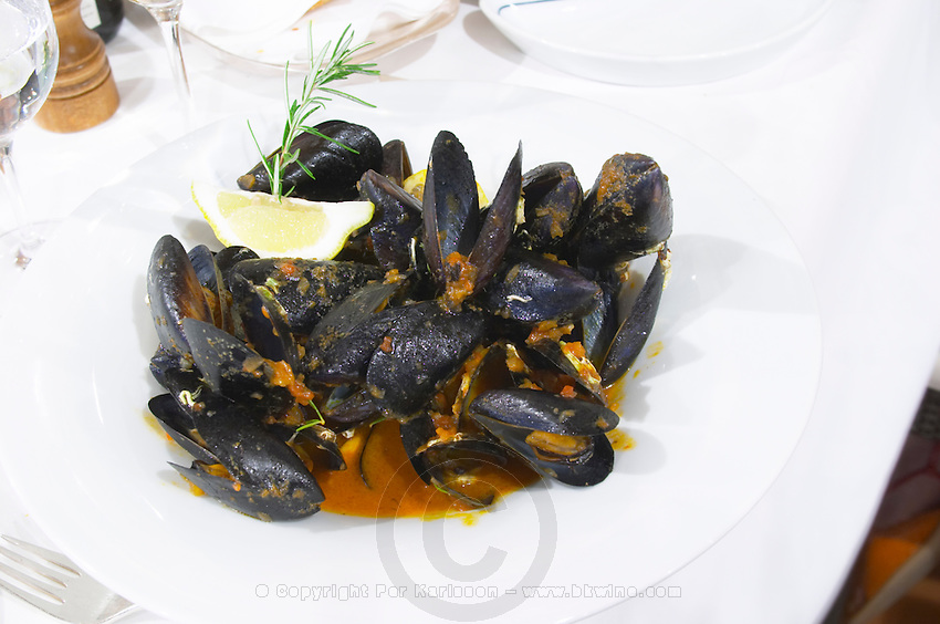 Mussels served in the shell with a red tomato sauce on a white plate from the luxury Excelsior Hotel and Spa restaurant terrace Dubrovnik, old city. Dalmatian Coast, Croatia, Europe.