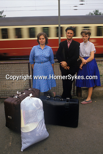 Friedland refugee camp West Germany. 1980's. Soviet-Germans return as refuges from the Soviet Union to freedom in the west. Having been processed documents checked etc this family wait at the train station with their belongings for a train to take them to a new life.