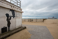 Banksy: Young girl with a suitcase looking through a telescope with a vulture perched on it staring down near a Calais beach points towards Britain.<br />