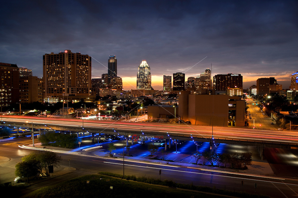 Sunset falls on the downtown Austin Skyline as the I-35 Makeover Project Parking garage performs its colored light show in blue.